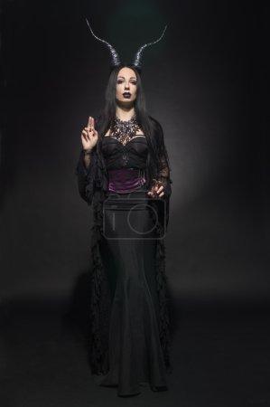 Photo pour Jeune femme en costume de fantaisie noir avec grandes cornes sur fond foncé - image libre de droit