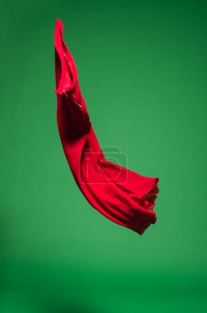 Photo for Red fabric in the air on green background - Royalty Free Image