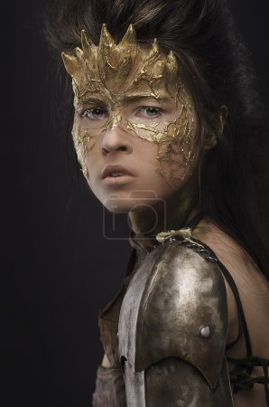 Photo for Woman in golden fantasy armour on black background - Royalty Free Image
