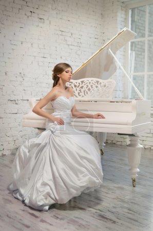 Photo pour Belle mariée en robe blanche jouant du piano - image libre de droit