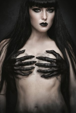 Woman with black demon hands on breast
