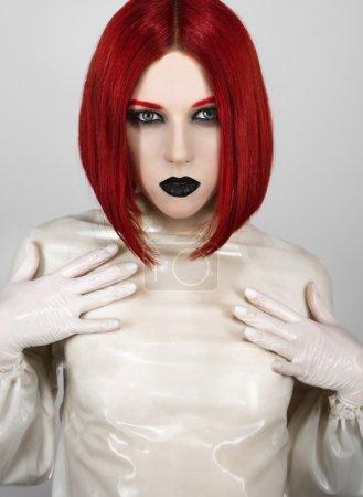 Photo pour Femme aux cheveux rouge et des lèvres noirs en latex chemisier - image libre de droit