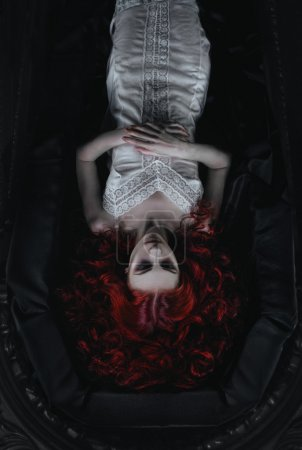 Female vampire lying in the coffin on the night ce...
