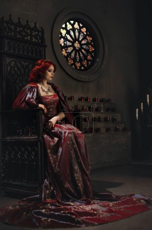 Photo pour Woman with red hair wearing elegant royal garb and golden crown sitting on a throne in ancient castle - image libre de droit