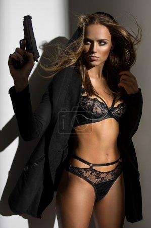 Photo pour Femme sexy en lingerie noire avec pistolet sur fond blanc - image libre de droit