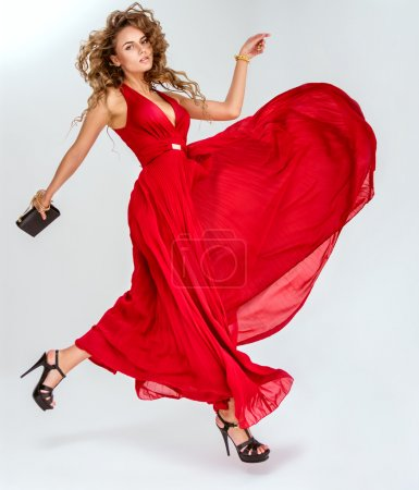 Photo for Posh sexy woman in long red dress over white background - Royalty Free Image