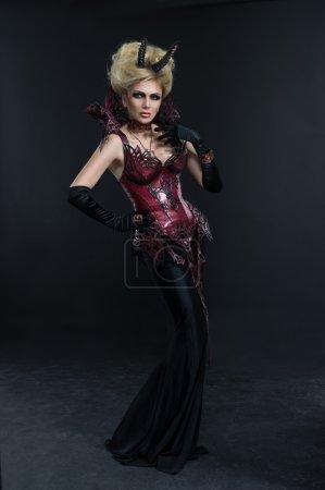 Photo pour Portrait de femme beau diable en robe sexy noire en studio - image libre de droit