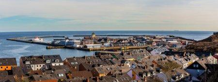 Photo pour Couleurs huches de pêcheur de crabe au port de l'île de Helgoland (Allemagne), maisons de style nordique avec bateau et ciel bleu, vue panoramique depuis la colline de la mer du Nord - image libre de droit