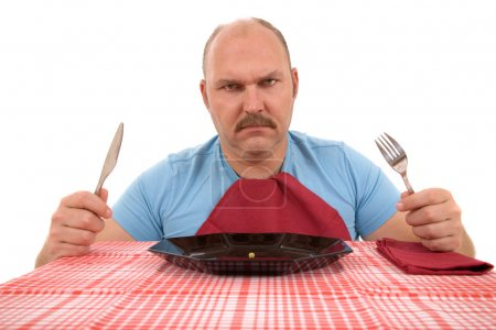 Photo for Mature man looking very angry with the content of his plate - Royalty Free Image