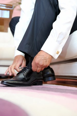 Groom dresses and binds shoes before the wedding