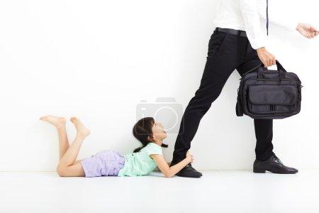 Photo pour Petite fille tenant les jambes de son père avant d'aller au travail - image libre de droit