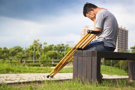 Photo pour Homme blessé avec des béquilles assis sur un banc - image libre de droit