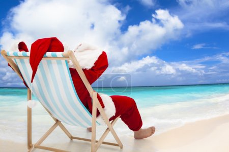 Photo for Santa Claus sitting on beach chairs with blue sky and cloud.Christmas Day concept. - Royalty Free Image