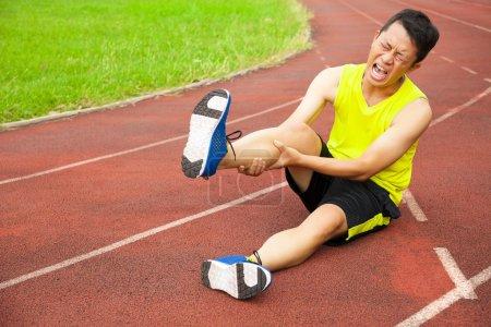 Photo pour Jeune coureur masculin souffrant de crampes aux jambes sur la piste dans le stade - image libre de droit