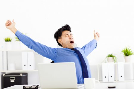 young businessman yawning at work in office