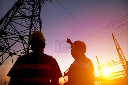 Photo for Two worker watching the power tower and substation with sunset background - Royalty Free Image