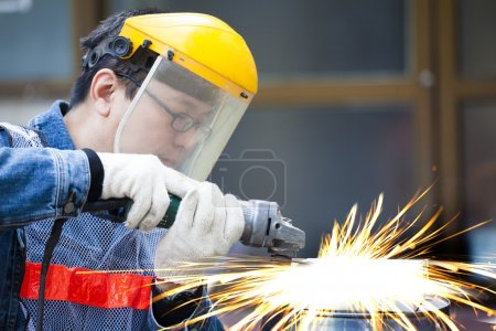 Worker with grinder machine cutting metal in factory