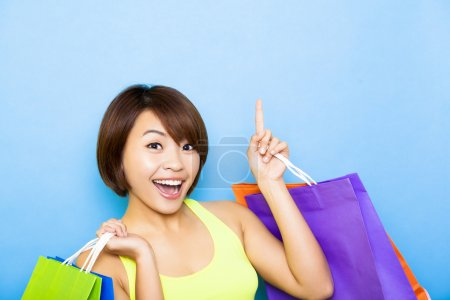 Photo for Young  woman holding shopping bags and pointing up - Royalty Free Image