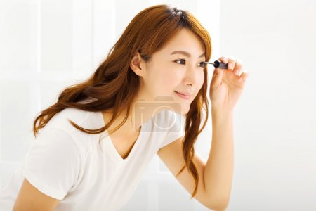 young beautiful Applying mascara in bedroom