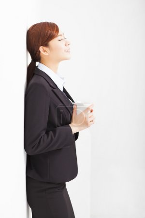 relaxed businesswoman leaning against white wall in office