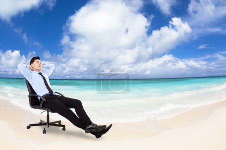 Photo for Relaxed Young businessman sitting in a chair with beach background - Royalty Free Image