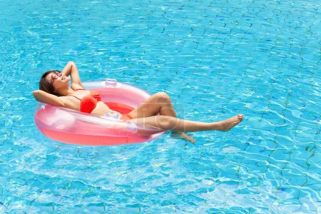 Photo for Young woman relaxing in swimming pool - Royalty Free Image
