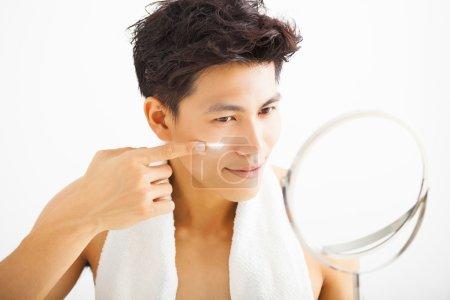 smiling man applying cream lotion on face