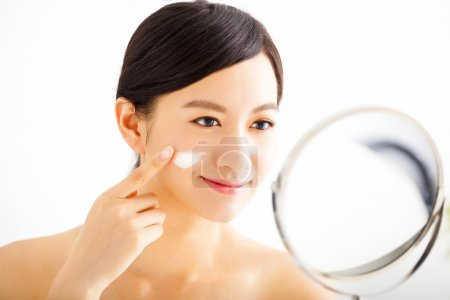 Photo for Smiling woman applying cream lotion on face - Royalty Free Image