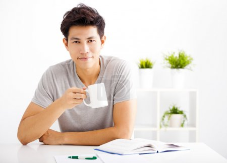 Photo for Smiling  young man reading  book  and drinking coffee - Royalty Free Image
