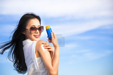 Photo for Young woman applying sun protection lotion - Royalty Free Image