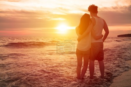 Photo for Young couple watching sunset on the beach - Royalty Free Image