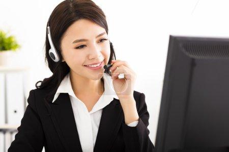 Photo pour Jeune belle femme d'affaires avec casque dans le bureau - image libre de droit