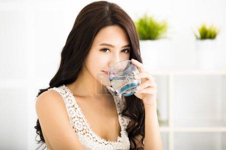 Photo pour Jeune femme souriante détendue boire de l'eau potable - image libre de droit