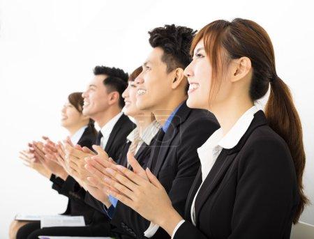 Photo pour Assis dans une rangée et à applaudir les gens d'affaires - image libre de droit