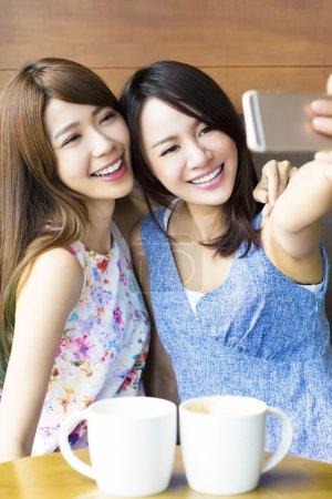 Photo pour Copines heureuses prenant un selfie dans un café - image libre de droit