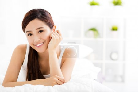 smiling young asian woman  on the bed