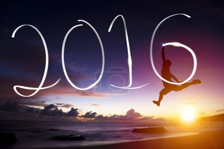 Photo for Happy new year 2016.young man jumping  and drawing 2016 on beach - Royalty Free Image
