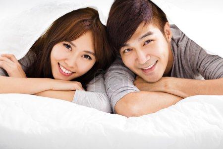 Photo pour Heureux jeune couple couché dans un lit - image libre de droit
