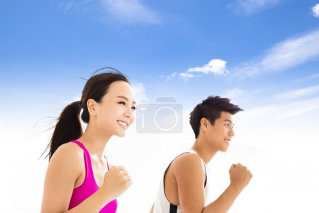 happy  young couple jogging against cloudy sky