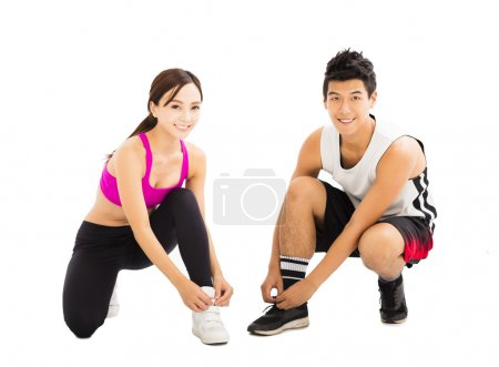 Woman and man tying sports shoes before workout