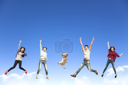 Photo for Happy young group jumping together with dog - Royalty Free Image