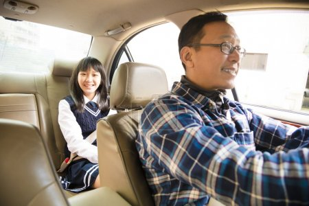 father driving to school with teen daughter