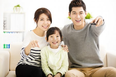 Photo for Happy Attractive Young  Family watching the tv - Royalty Free Image