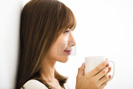 Photo pour Jeune femme buvant du café latte chaud dans le salon - image libre de droit
