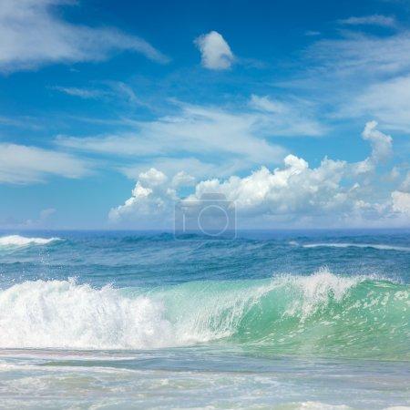 Photo pour De belles vagues dans l'eau chaude de la mer et le ciel bleu avec des nuages légers, se détendre à l'heure d'été - image libre de droit
