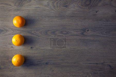 Three Oranges are on empty dark Wooden Table