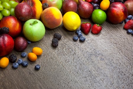Photo for Border of mixed fruits with water drops on beautiful wooden texture - copy space - Royalty Free Image
