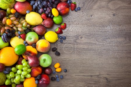 Different Organic Fruits  with  water drops on wooden table back