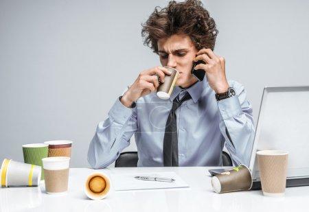 Foto de Café y conversación: Mientras habla intensamente por teléfono, el gerente se sienta con una taza. Moderno oficinista en el lugar de trabajo, perezosa y el concepto de pereza - Imagen libre de derechos