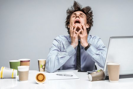Photo for OMG! Frustrated man sitting desperate over paper work at desk. Negative emotion facial expression feeling - Royalty Free Image